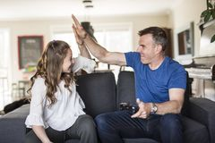 Handsome father and his cute little daughter are playing game console and smiling while sitting on couch at home. Royalty Free Stock Photos
