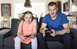 Handsome father and his cute little daughter are playing game console and smiling while sitting on couch at home. Royalty Free Stock Photography