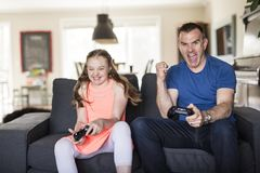 Handsome father and his cute little daughter are playing game console and smiling while sitting on couch at home. Stock Photo