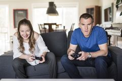 Handsome father and his cute little daughter are playing game console and smiling while sitting on couch at home. Stock Images