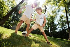 Handsome father and his little son dressed in the white t-shirts are playing football on a lawn on a warm day. stock photo