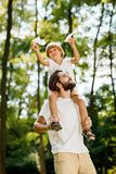 Handsome father and his little son walking in the forest. Boy is sitting on the shoulders of his father and keeps a royalty free stock photos