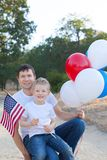 Handsome father holding colorful balloons and his little son hol Royalty Free Stock Photo