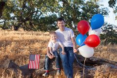Handsome father holding colorful balloons and his little son hol Stock Images