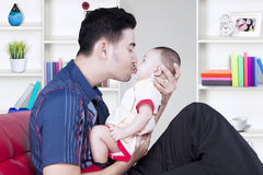 Handsome father kissing baby boy Royalty Free Stock Images