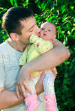 Handsome father kissing his baby. Handsome young father kissing his little baby on green tree background Royalty Free Stock Images
