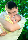 Handsome father kissing little baby stock photo