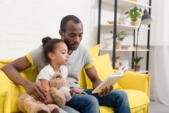 handsome father and little daughter reading book together stock photo