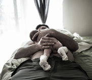 Handsome father is lying on the bed and holding with care his sweet new born baby son. On  body Royalty Free Stock Photography