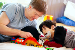 Handsome father playing cars with disabled son. On floor mat Stock Image