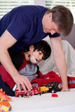 Handsome father playing cars with disabled son. On floor mat Stock Images