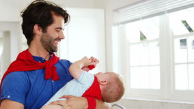 Handsome father playing with his baby stock footage