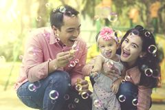 Handsome father playing soap bubbles with daughter Stock Photos