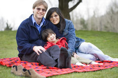 Handsome father sitting at park with disabled son Royalty Free Stock Photography