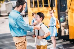 handsome father talking to his son before school in front of school bus royalty free stock photo