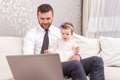 Handsome father working with laptop Stock Photos