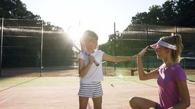 Handsome female coach giving five to little tennis player after tennis training on the court. Handsome female coach giving five to little tennis player after stock video footage