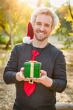 Handsome Festive Young Caucasian Man Holding Christmas Gift. Outdoors royalty free stock photos