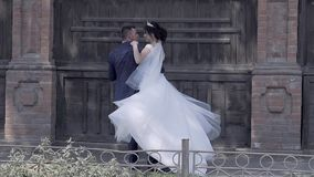 Handsome fiance holds and spins bride in long white dress stock video