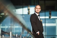 Handsome fiance leaning on modern handrails leaning. Handsome elegant fiance leaning on modern metal handrails holding hands in pockets of elegant suit royalty free stock photo