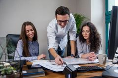 Handsome firm manager in glasses explains work tasks for his employees. Creative people or advertising business concept. Young firm manager explains work tasks stock photos