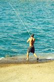 Handsome fisherman fishes with fishing rod royalty free stock images