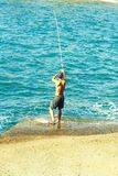Handsome fisherman fishes with fishing rod stock photo