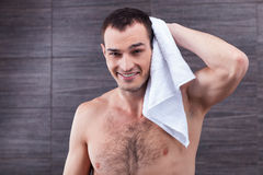 Handsome fit guy is drying himself after bathing Royalty Free Stock Photos