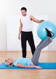 Instructor helping a woman with pilates exercises Stock Photos