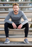 Handsome fit man with beard sitting on steps outside. Portrait of a handsome fit man with beard sitting on steps outside Stock Photography