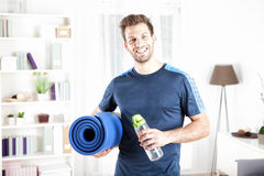 Handsome Fit Man Holding Mat and Bottle of Water Royalty Free Stock Photography