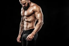 Handsome fit man posing wearing in jeans with tattoo. Sport and fashion concept isolated on black background. Tattoo man bodybuilder. Action shot with copy Stock Photography