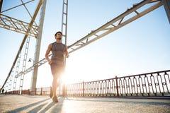 Handsome fit man running fast along big modern bridge Royalty Free Stock Image