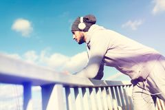 Man runner taking a break after intensive training outdoors, listening music on his mobile smart phone. Handsome fit man taking a break after intensive training Royalty Free Stock Photo
