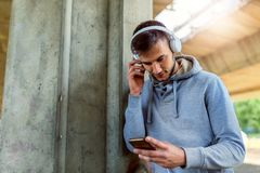 Handsome fit man taking a break after intensive training outdoors, texting on his smart phone wearing headphones. Intensive training outdoors Stock Photos