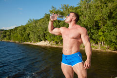 Handsome fit muscular man drink water on beach Stock Images