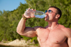 Handsome fit muscular man drink water on beach Royalty Free Stock Image