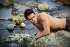 Handsome fit shirtless young man laying on rock Stock Image
