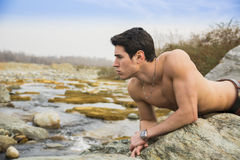 Handsome fit shirtless young man laying on rock Royalty Free Stock Photos