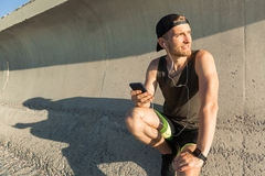 Handsome fit sportsman listening to music with earphones Royalty Free Stock Photos