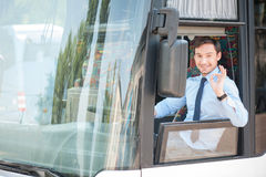 Handsome fit young driver is gesturing positively. Cheerful man is driving a bus with enjoyment. He is showing okay sign and smiling. The man is looking through Stock Photography