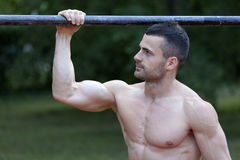 Handsome fit young man doing exercises on the horizontal bar and Royalty Free Stock Photos