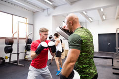 Handsome fit young man in gym boxing with his trainer. Stock Images
