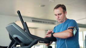 Handsome fit young man in gym doing exercises on exercise bike. Using his smartwatch checking vitals stock video