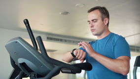 Handsome fit young man in gym doing exercises on exercise bike. Using his smartwatch checking vitals stock video footage