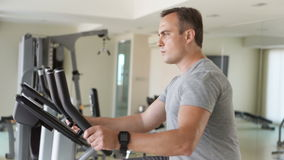 Handsome fit young man in gym doing exercises on exercise bike. Using his smartwatch checking vitals stock footage