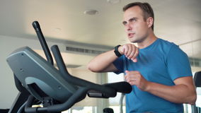 Handsome fit young man in gym doing exercises on exercise bike. Using his smartwatch sending message stock video