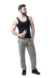 Handsome fit young man holding water bottle container looking away. Full body length portrait isolated over white studio background Royalty Free Stock Photo