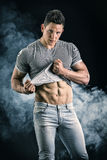 Handsome, fit young man pulling up t-shirt Stock Images