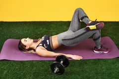 Handsome fit young woman do exercise with dumbbells on the fitness purple mat on green grass over yellow background. Handsome fit young woman do exercise with stock images